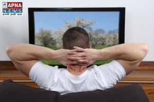 Young man sitting on a sofa and watching tv